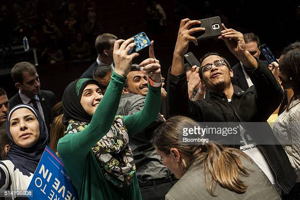 Attendees take selfie photographs before the start of a campaign event for Senator Bernie Sanders an independent from Vermont and 2016 Democratic...