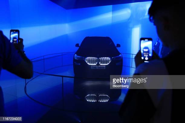 Attendees take smartphone photographs of a new BMW X6 M50i automobile at the Bayerische Motoren Werke AG exhibition hall on the opening day of the...
