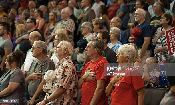 Attendees take the Pledge of Allegiance before Republican candidate for President Donald Trump speaks at a rally at Erie Insurance Arena on August...