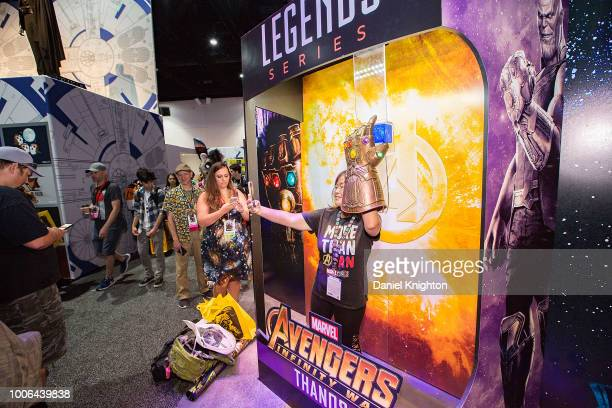 Attendees take turns posing for photos inside a lifesize action figure box at the Hasbro Toy booth at ComicCon International on July 20 2018 in San...