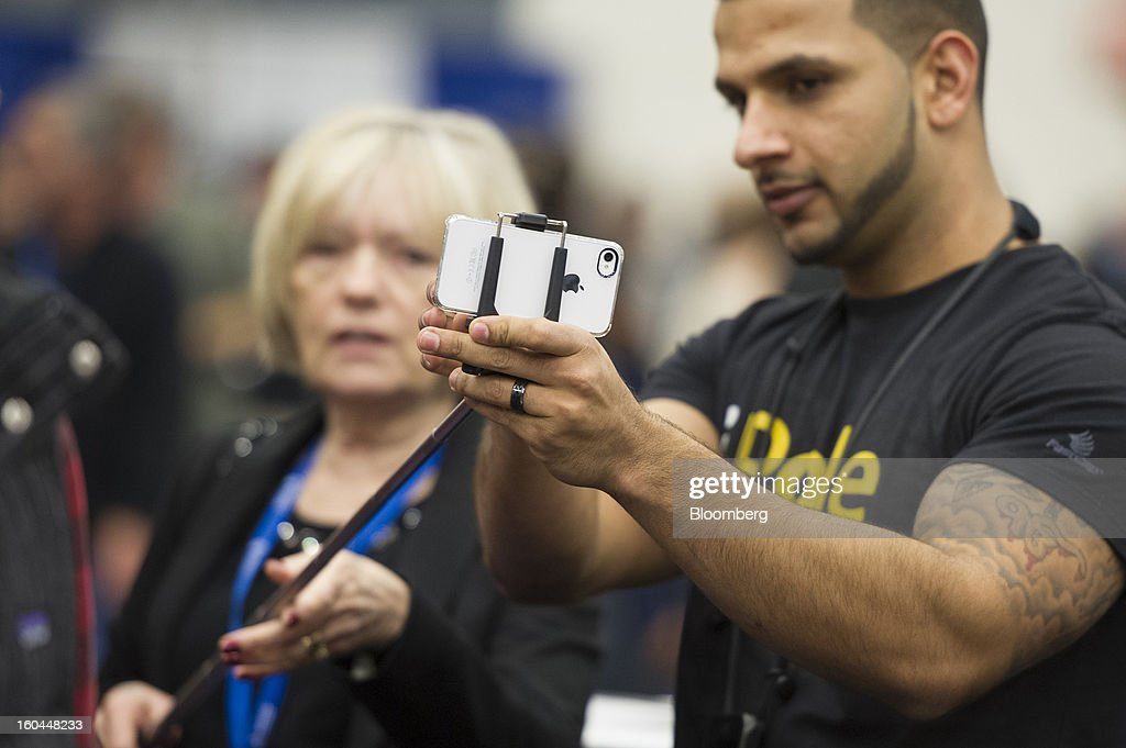 Attendees try out FastCap Tech's iPole Mini camera pole with an Apple Inc. iPhone at the Macworld/iWorld conference at the Moscone Center West in San Francisco, California, U.S., on Thursday, Jan. 31, 2013. This year's conference, titled 'The Ultimate iFANEvent,' brings together attendees to celebrate Apple Inc. technology and learn more about products and services for Apple users. Photographer: David Paul Morris/Bloomberg via Getty Images