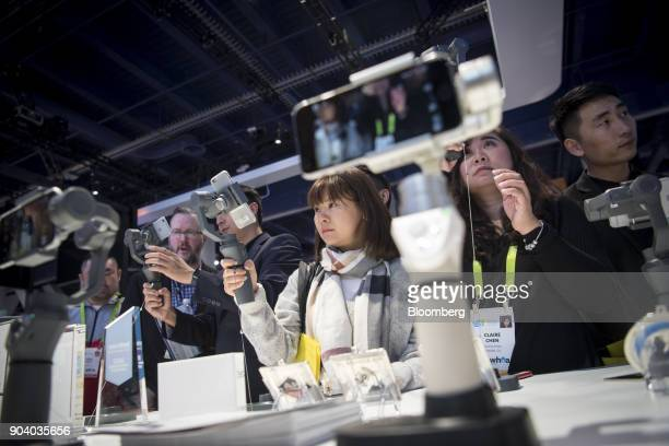 Attendees try out the SZDJITechnology Co Osmo smartphone stabilizer during the 2018 Consumer Electronics Show in Las Vegas Nevada US on Thursday...