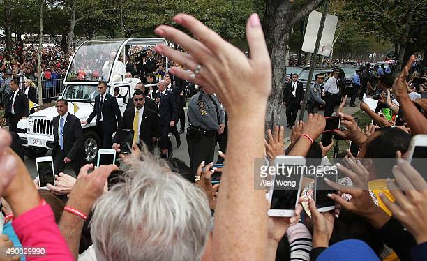Attendees try to catch a glimpse as Pope Francis greets them from the popemobile prior to the Mass for the conclusion of the World Meeting of...