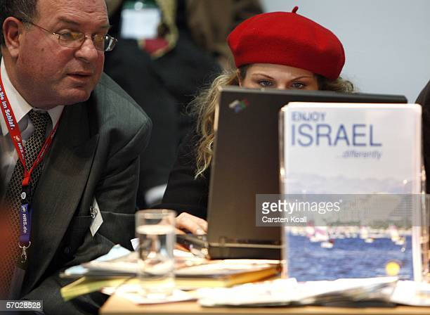 Attendees use a computer as they speak to one another at the stand of Israel on the opening day of the Internationale Tourismus Boerse fair on March...
