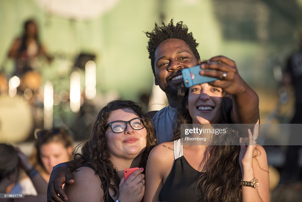 Attendees use an Apple Inc. iPhone to take a selfie photograph at a concert at Spotify House during the South By Southwest (SXSW) Interactive Festival at the Austin Convention Center in Austin, Texas, U.S., on Monday, March 14, 2016. The SXSW Interactive Festival features presentations and panels from the brightest minds in emerging technology, scores of networking events hosted by industry leaders and a lineup of special programs showcasing new websites, video games, and startup ideas. Photographer: David Paul Morris/Bloomberg via Getty Images
