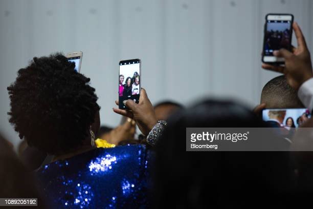 Attendees use mobile devices to take photographs of Senator Kamala Harris a Democrat from California not pictured during the Alpha Kappa Alpha...