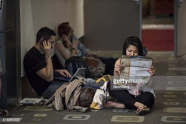 Attendees use mobile phone and check locations on a map inside the Austin Convention Center during the South By Southwest Interactive Festival in...