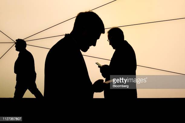 Attendees use mobile phones as they pass a Samsung Networks sign outside the Samsung Electronics Co pavilion on the opening day of the MWC Barcelona...
