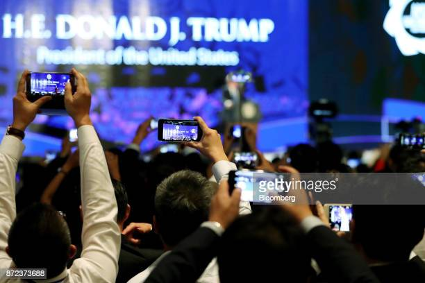 Attendees use smartphones to photograph US President Donald Trump not pictured speaking at the AsiaPacific Economic Cooperation CEO Summit in Danang...