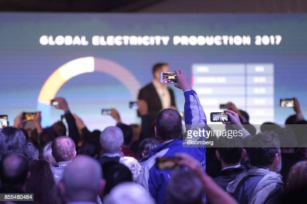 Attendees use smartphones to record Elon Musk cofounder and chief executive officer of Tesla Inc as he speaks during an event at the Hornsdale wind...