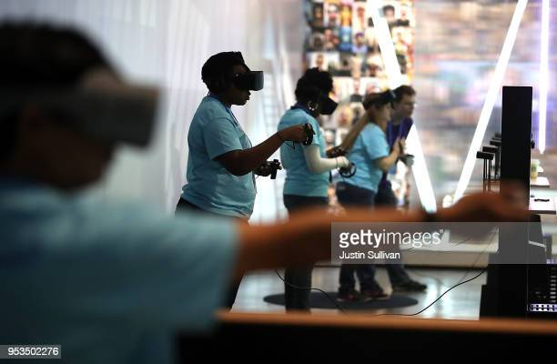 Attendees use the Oculus Go VR headset during the F8 Facebook Developers conference on May 1 2018 in San Jose California Facebook CEO Mark Zuckerberg...