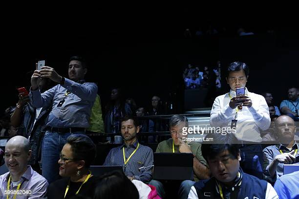 Attendees use their phone prior to the Apple launch event on September 7 2016 in San Francisco California Apple Inc is expected to unveil latest...