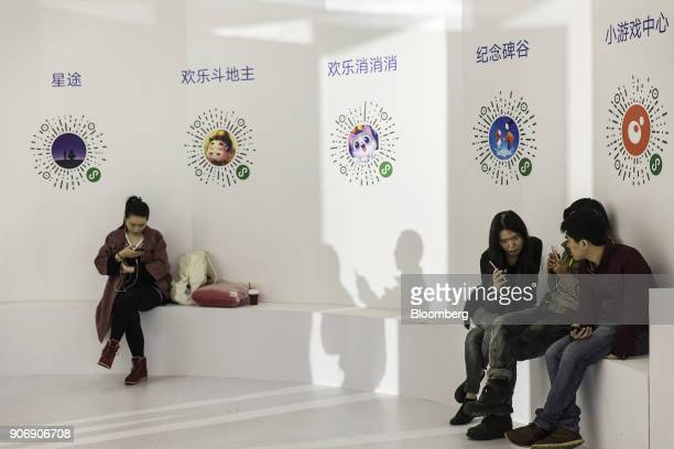 Attendees use their smartphones as QR codes for various inapp games are displayed on a wall at Tencent Holdings Ltd's WeChat Open Class Pro...