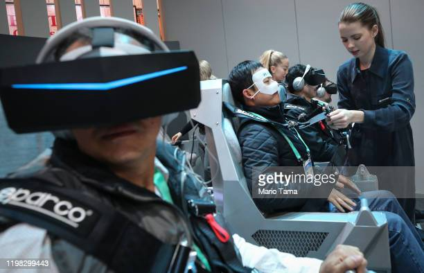 Attendees use virtual reality headsets to experience Hyundai and Uber's air taxi SAI at CES 2020 at the Las Vegas Convention Center on January 8 2020...
