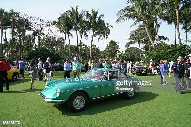 Attendees view a 1967 Ferrari SpA 330 GTC Speciale sports vehicle on display during the 26th Annual Cavallino Classic Event at the Breakers Hotel in...