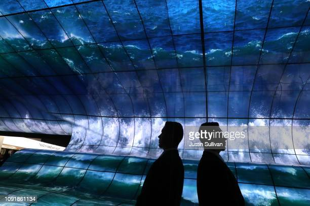 Attendees view a wall 250 curved LG OLED TVs at the LG booth during CES 2019 at the Las Vegas Convention Center on January 9 2019 in Las Vegas Nevada...