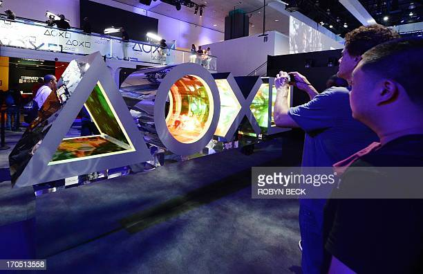 Attendees view an installation of the Sony Playstation controller symbols with video inside the shapes at the E3 Electronic Entertainment Expo in Los...