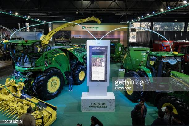 Attendees view Deere Co John Deere farm machinery at the exhibition pavilion during La Exposicion Rural agricultural and livestock show in the...