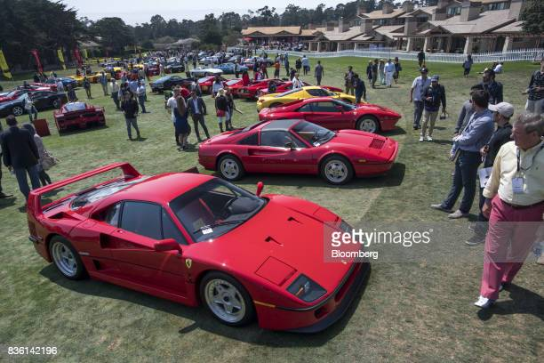 Attendees view Ferrari NV vehicles on display at the Ferrari Concours at the company's special 70th anniversary eventduring the 2017 Pebble Beach...