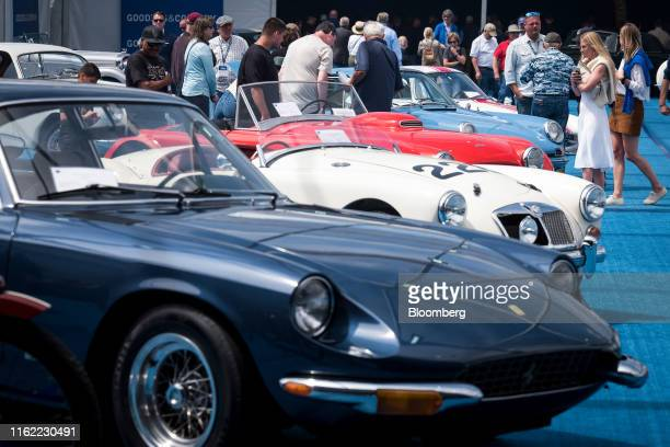 Attendees view vehicles on display at the Gooding and Company auction at the 2019 Pebble Beach Concours d'Elegance in Pebble Beach, California, U.S.,...