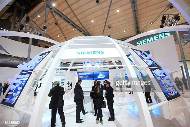 Attendees visit the Siemens AG exhibition trade stand at the Hanover industrial fair in Hanover Germany on Monday April 13 2015 Indian Prime Minister...