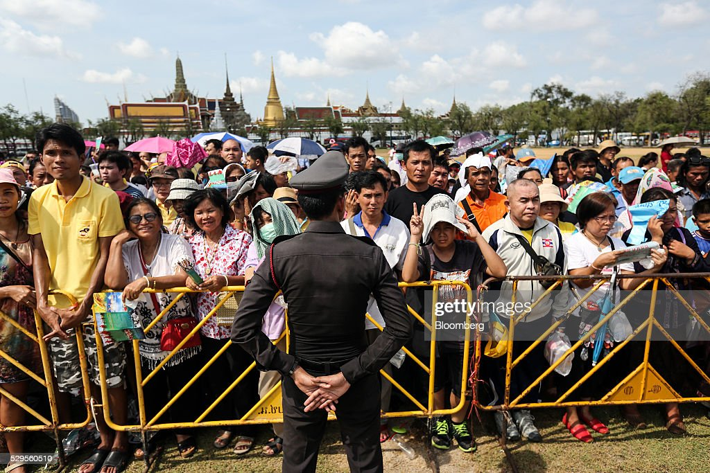 Attendees wait behind barriers waiting to collect 'sacred' rice grains from the ground after the Royal Ploughing Ceremony at Sanam Luang park in Bangkok, Thailand, on Monday, May 9, 2016. This year may be a better one for Thai rice production. At least, that's what two sacred oxen and a ceremonial lord forecast at an annual ploughing ceremony. Photographer: Dario Pignatelli/Bloomberg via Getty Images