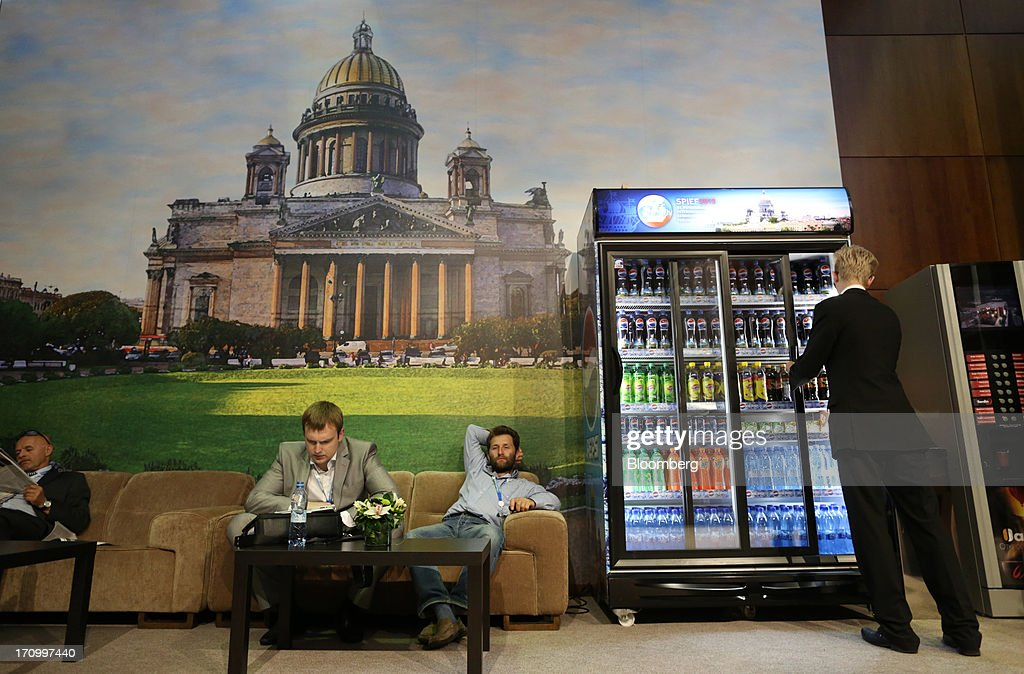 Attendees wait in a lounge area while an employee restocks a drinks cabinet on the opening day of the St. Petersburg International Economic Forum 2013 (SPIEF) in St. Petersburg, Russia, on Thursday, June 20, 2013. Russian consumer spending probably eased and investment shrank at the fastest pace since 2011, adding to evidence the $2 trillion economy is stalling. Photographer: Andrey Rudakov/Bloomberg via Getty Images
