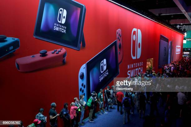 Attendees wait in line underneath Nintendo Co signage displayed during the E3 Electronic Entertainment Expo in Los Angeles California US on Wednesday...