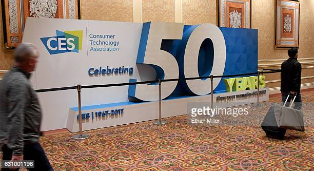 Attendees walk by a sign marking the 50th anniversary of CES at The Venetian Las Vegas on January 4 2017 in Las Vegas Nevada CES the world's largest...