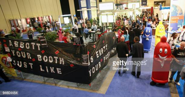 Attendees walk by an exhibition space reserved by Abbott Laboratories at the 16th International AIDS Conference August 15 2006 in Toronto Ontario...