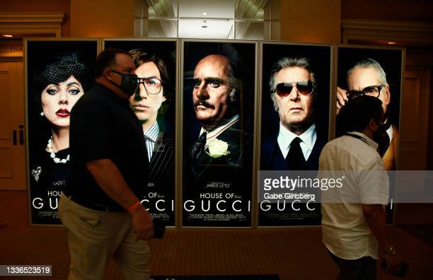 """Attendees walk by an illuminated advertisement for the upcoming """"House of Gucci"""" movie display at Caesars Palace during CinemaCon, the official..."""