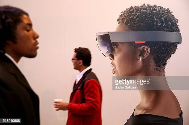 Attendees walk by an image of the Microsoft HoloLens augmented reality viewer during the 2016 Microsoft Build Developer Conference on March 30 2016...