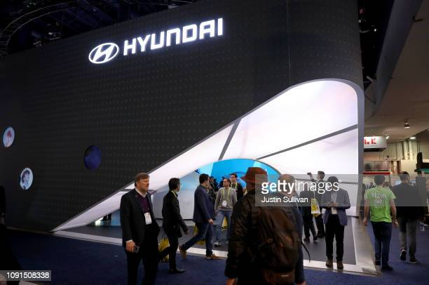 Attendees walk by the Hyundai booth during CES 2019 at the Las Vegas Convention Center on January 8 2019 in Las Vegas Nevada CES the world's largest...