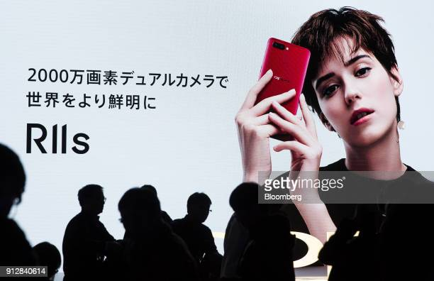 Attendees walk in front of an advertisement during a launch event for the Oppo R11s smartphone for the Japanese market in Tokyo Japan on Wednesday...