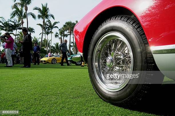 Attendees walk on the green as the wheel of a Ferrari SpA vehicle is seen during the 26th Annual Cavallino Classic Event at the Breakers Hotel in...