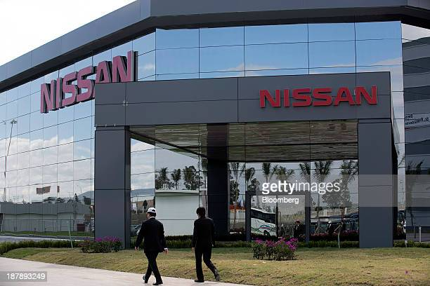 Attendees walk outside one of the buildings during a ceremony for the opening of a new Nissan Motor Co assembly plant in Aguascalientes Mexico on...