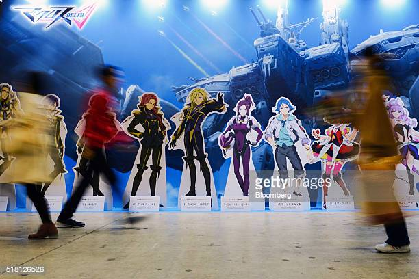 Attendees walk past a display at the Anime Japan 2016 convention in Tokyo Japan on Saturday March 26 2016 In it's third year the three day convention...