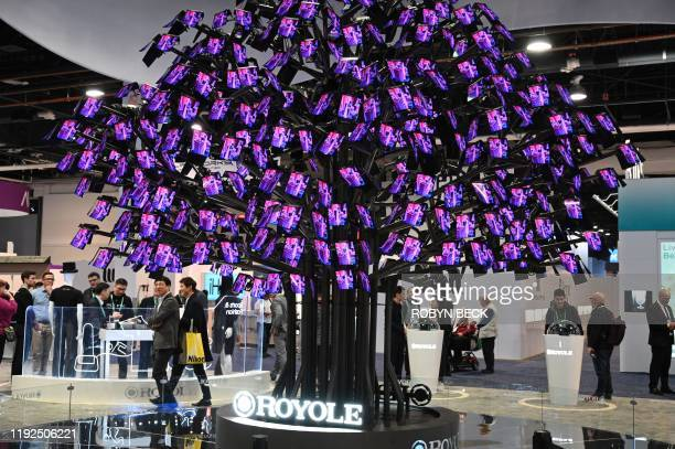 Attendees walk past a display of Royole FlexPai foldable smartphonesat the January 7 2020 at the 2020 Consumer Electronics Show in Las Vegas Nevada