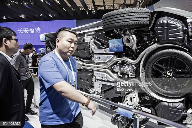 Attendees walk past a display showing the undercarriage of a Ford Motor Co Edge sport utility vehicle at the Beijing International Automotive...