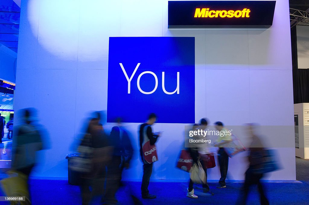 Attendees walk past a Microsoft Corp. signage displayed at the International Consumer Electronics Show (CES) in Las Vegas, Nevada, U.S., on Friday, Jan. 13, 2012. The 2012 CES trade show, which runs through Jan 13, features more than 2,700 global technology companies presenting consumer tech products and is expected to draw over 140,000 attendees. Photographer: David Paul Morris/Bloomberg via Getty Images
