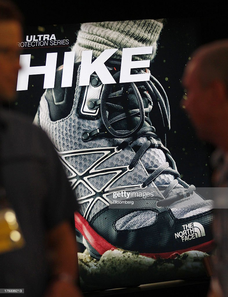 Attendees walk past a North Face Inc. advertisement displayed at the company's booth during the Outdoor Retailer Summer Market show in Salt Lake City, Utah, U.S., on Thursday, Aug. 1, 2013. Consumer spending in the U.S. rose in line with forecasts in June as Americans' incomes grew, a sign the biggest part of the economy is withstanding fiscal headwinds. Photographer: George Frey/Bloomberg via Getty Images