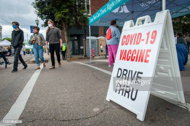 Attendees walk past a pop-up Covid-19 vaccine site at the Juke Joint Festival in Clarksdale, Mississippi, U.S., on Saturday, April 17, 2021. In 2020,...