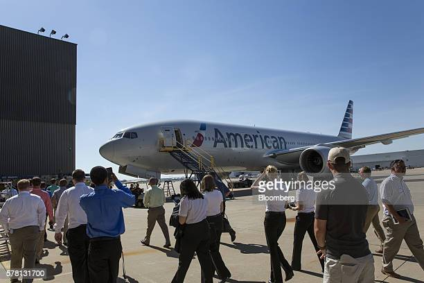 Attendees walk past an American Airlines Inc aircraft while on a tour of an airport hangar at DallasFort Worth International Airport during a...