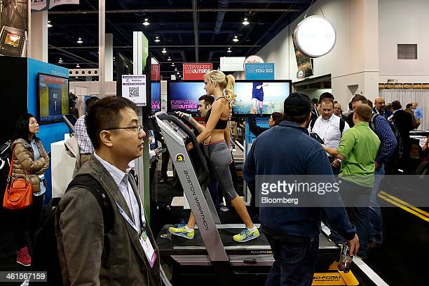 Attendees walk past an exhibitor demonstrating the iFit Everywhere Inside treadmill at the 2014 Consumer Electronics Show in Las Vegas Nevada US on...