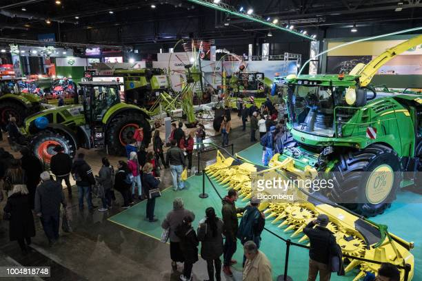 Attendees walk past Deere Co John Deere farm machinery at the exhibition pavilion during La Exposicion Rural agricultural and livestock show in the...