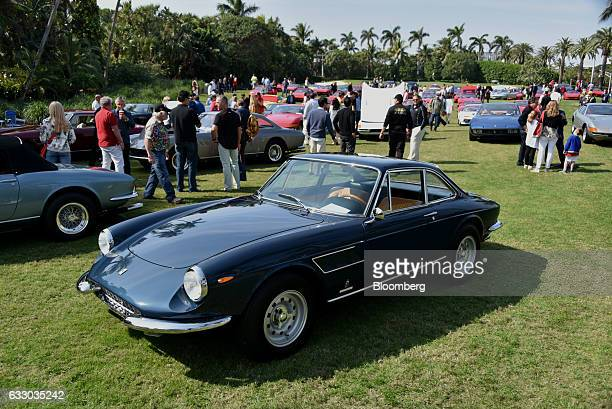 Attendees walk past Ferrari SpA vehicles on display during the 26th Annual Cavallino Classic Event at the Breakers Hotel in Palm Beach, Florida,...