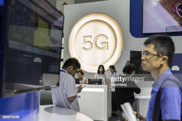 Attendees walk past signage for 5G at the Qualcomm Inc booth at the Mobile World Congress Shanghai in Shanghai China on Thursday June 28 2018 The...