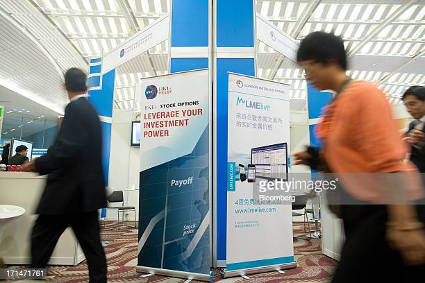 Attendees walk past signage for the London Metal Exchange LMElive the exchanges realtime price and data system and Hong Kong Exchanges Clearing Ltd...
