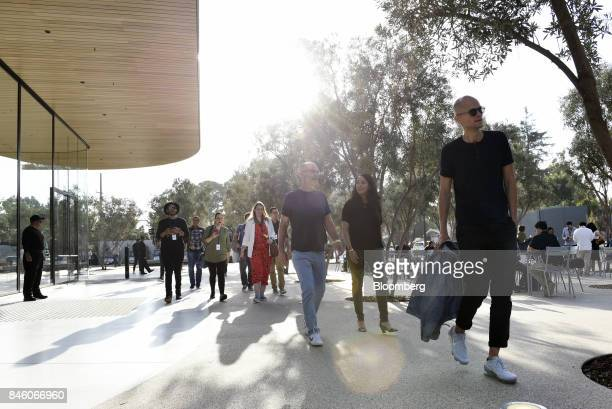 Attendees walk past the Apple Visitors Center ahead of an event at the Steve Jobs Theater in Cupertino California US on Tuesday Sept 12 2017 Apple...
