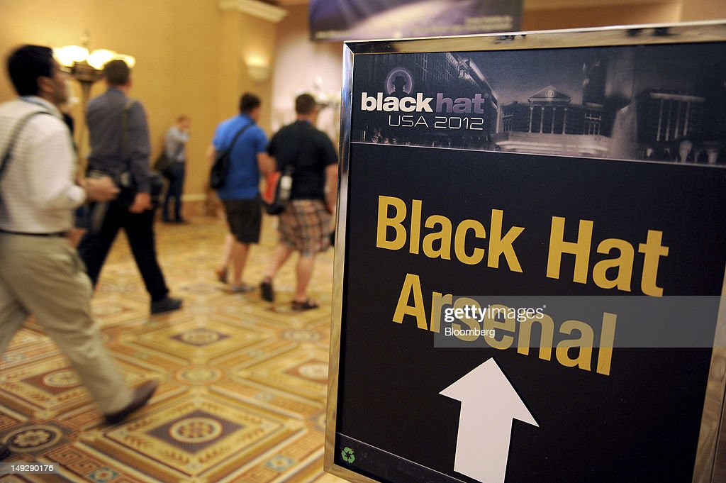 Attendees walk past the Arsenal Tools booth during the Black Hat USA 2012 conference at Caesar's Palace resort and casino in Las Vegas, Nevada, U.S., on Wednesday, July 25, 2012. The conference brings together leaders from all facets of the information security world, from corporate and government sectors to academic and even underground researchers. Photographer: Jacob Kepler/Bloomberg via Getty Images